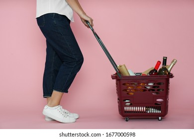 Woman with shopping basket full of different products on pink background, closeup