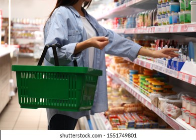 Woman with shopping basket in supermarket, closeup