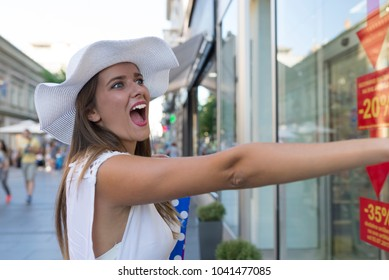 Woman shopping in Belgrade and looking at a shop window. Beautiful girl standing and looking at clothes to buy. Lifestyle and shopping concepts.