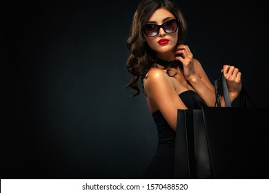 Woman at shopping. Black Friday sale concept for shops. Happy smiling girl in sunglasses holding big bag isolated on dark background at shopping.