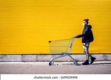 Woman with a shopping cart in front of a store, wearing a mask during a coronavirus pandemic / Covid-19.