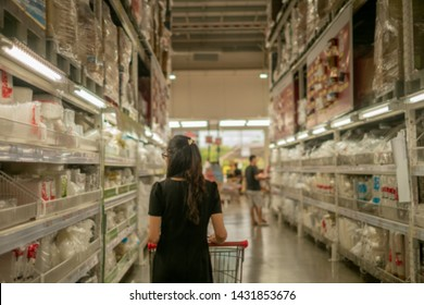 Woman with shopping cart or trolley buying food and product at grocery store or supermarke,Consumerism and people concept .Abstrat blure supermarket retail and shopping mall interior for background.