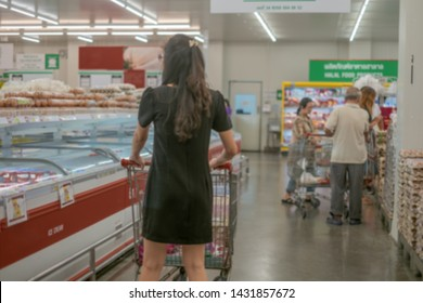 Woman with shopping cart or trolley buying food and product at grocery store or supermarke,Consumerism and people concept . .Abstrat blure supermarket retail and shopping mall interior for background.