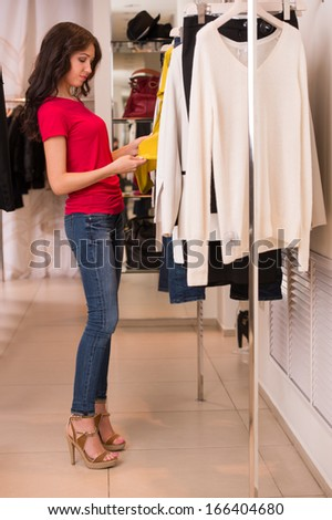 3996293754 Woman shopping choosing dresses. Beautiful young shopper in clothing store.  Full length