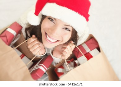 d8cbd53b484d7 Woman shopping for christmas gifts. Young asian caucasian girl looking up  smiling with shopping bags