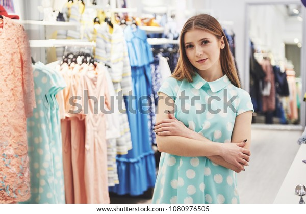 299c0e04ed5fd Woman shopping clothes. Shopper looking at clothing indoors in store.  Beautiful happy smiling caucasian