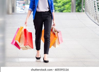 Woman shopping concept, asian woman holding colorful shopping bags walking in the city/shopping mall, happy funny feeling