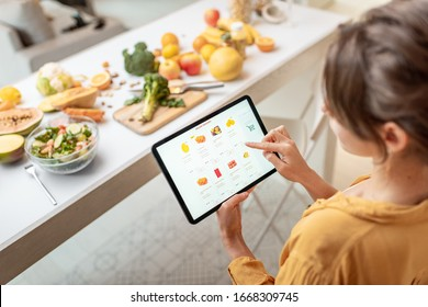 Woman shopping food online using a digital tablet at the kitchen. Concept of buying online using mobile devices