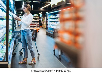 Woman shopping at the grocery store, by the refrigerator