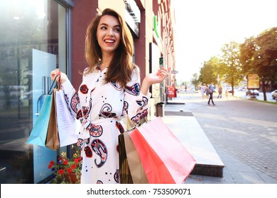 Woman Shopping. Happy woman holding shopping bags and smiling at the mall