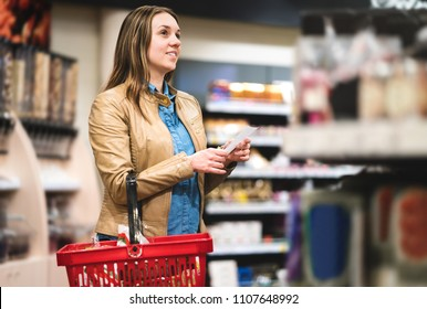 Woman with shopping list in supermarket and grocery store. Happy customer doing groceries with budget, plan or checklist. Lady buying food for family. Shopper with basket between shelves in aisle.