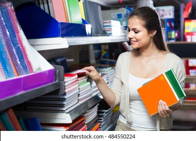 smiling woman shopping notebooks and writing paper in stationary store