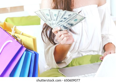Woman shopping online with laptop computer on bed at home