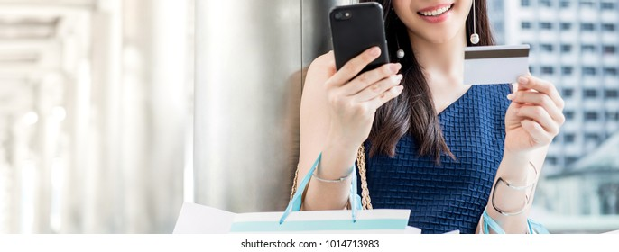 Woman shopping online and making payment digitally with credit card using mobile phone application, panoramic banner