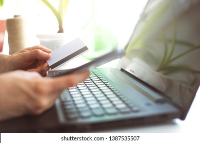 Woman shopping online with a smartphone. Hands of female buys online holding a credit card with a laptop on the table sitting in a cafe.