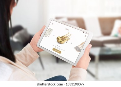 Woman shopping online with tablet. Modern commerce web site interface with shoes.