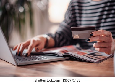 Woman shopping online and using credit card while reading cosmetic catalogue