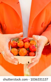 Woman shopping for organic vegetables produce at a farmers market. Close up of hands holding a pint basket with bright, fresh, ripe red and orange cherry tomatoes. Selective focus on tomatoes.