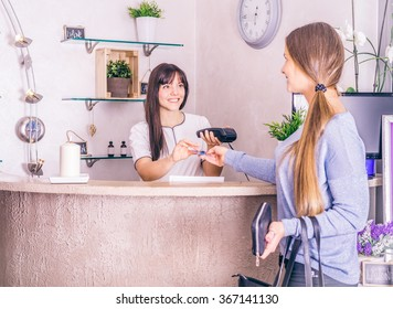 Woman shopping and paying with credit card in a shop - Customer paying with card for her purchase