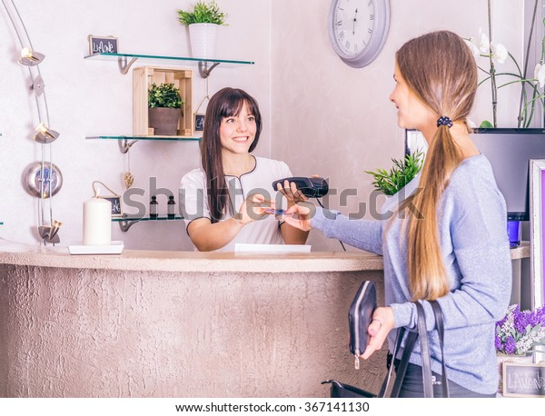 Frauen kaufen und bezahlen mit Kreditkarte im Geschäft - Kunde zahlt mit Karte für ihren Kauf