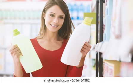 Woman shopping at the supermarket and comparing different products, she is holding two bottles of laundry detergent