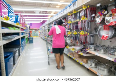 Woman Shopping in Supermarket or Hypermarket Household and Kitchen accessories section, Abstract Blur or Defocus Background.