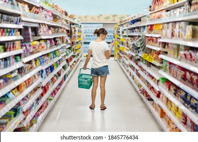 Woman shopping in a supermarket looking at the screen of phone