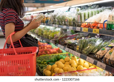 Woman shopping in supermarket reading product informationWoman shopping in supermarket reading product information
