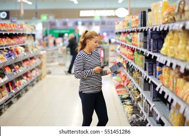 Woman shopping in supermarket reading product information