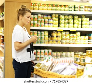 Woman shopping in supermarket reading product information. Checking list.Woman with a smartphone  choosing  a dairy products at supermarket