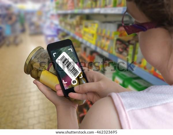 Una mujer está comprando en un supermercado y escaneando código de barras con smartphone en una tienda de comestibles para obtener información en línea sobre el producto.