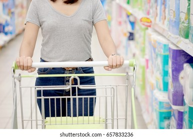 woman shopping at the supermarket, she is holding on a supermarket cart.