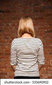 Woman with short blonde hair standing with her back to the camera in front of a brick wall