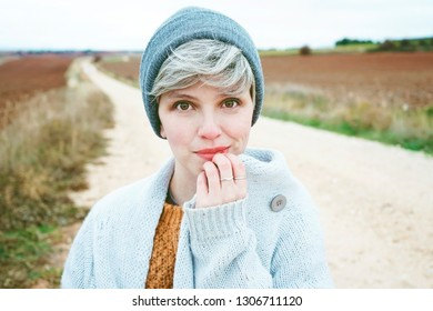 Woman with short and gray hair is alone in the beggining of a rural path in a cold autumn day