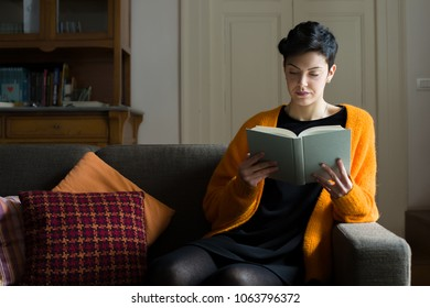 Woman with Short Hair Reading a Book on a Sofa