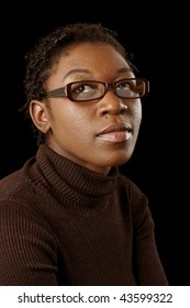 woman with short hair and spectacles looking up on black background