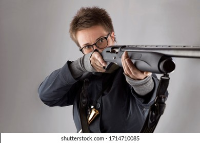 A woman with a short haircut, in glasses and a blue windbreaker shoots from a hunting rifle on a gray background.