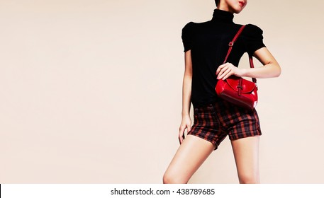 Woman with short pants and black high neck top holding red handbag purse. Fashion image.