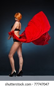 Woman with short red hair and black underwear holding fluttering red scarf with both hands up to wind.