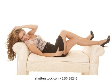 a woman in a short skirt laying on a bench.