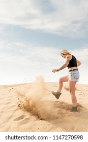 Woman in shorts in the desert digs sand with her foot, creating a cloud of dust