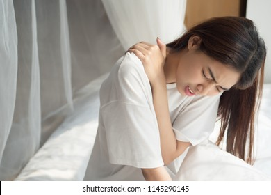 woman with shoulder or neck pain; portrait of asian woman suffering from shoulder or neck pain, stiffness, injury, chronic bone or muscle injury, body and health care concept; asian adult woman mode
