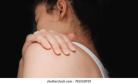 woman with shoulder pain .Acute pain in a woman muscle. Concept photo with read spot indicating location of the pain.