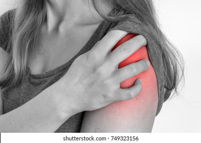Woman with shoulder pain is holding her aching arm - black and white photo