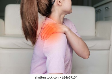 woman with shoulder pain or stiffness.Acute pain in a woman shoulder. Female holding hand to spot of shoulder-aches. Concept photo  with read spot indicating location of the pain.
