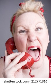 Woman shouting into red phone handset