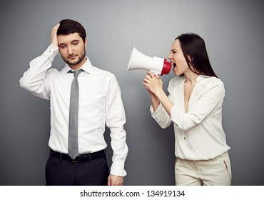 woman shouting in megaphone at the tired man. studio shot over dark background