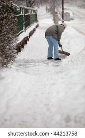 Woman shoveling snow from the sidewalk in front of her house after a heavy snowfall in a city