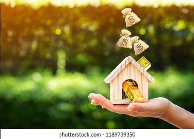 Woman show hand holding a model home and gold bar and dropping a money bag on sunlight in the public park, Saving money for buy a new house or loan for plan business investment of real estate concept.