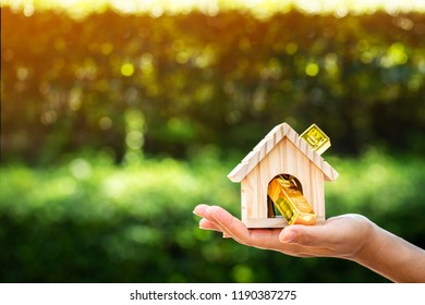 Woman show hand holding a model home and gold bar on sunlight in the public park, Saving money for buy a new house or loan for plan business investment for real estate concept.